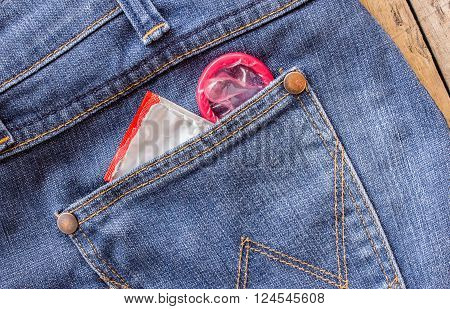 Condom in the blue jeans pocket on wooden table background