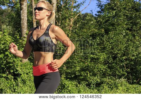 a sportive blond woman jogging in park
