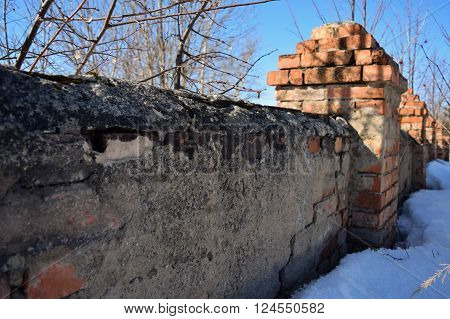old brick wall with turrets which began collapses