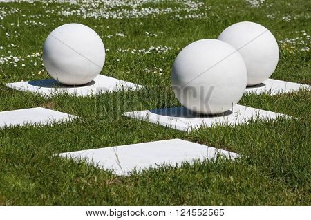 Abstract outdoor composition of white stable balls on bases in the grass