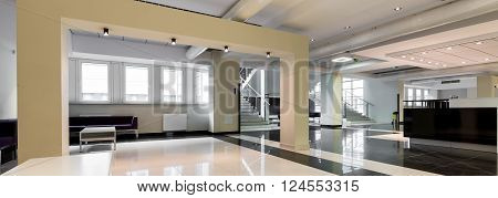 Big stylish entrance hall to modern university building. Two comfortable sofas in the corner