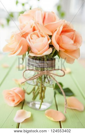 Peach colored roses in vintage glass jar