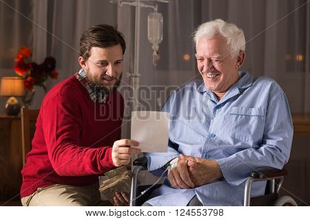Image of senior on wheelchair with son smiling together