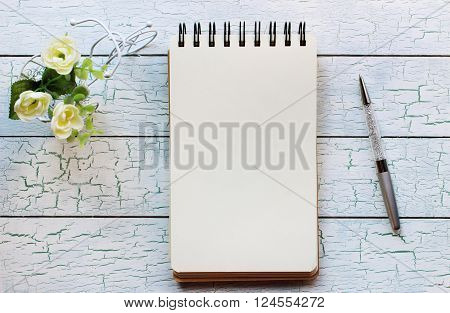Mockup for presentations with little bicycle notebook and a pen. Desktop workplace designer artist painter top view. Modern trend template for advertising.