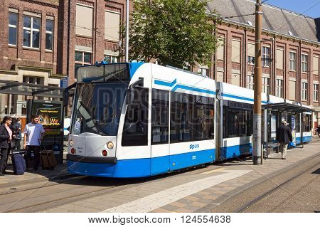 AMSTERDAM - AUG 27 2014: Public transport company GVB tram in front of Amsterdam Central Station. The city's Tram network is the largest tram network in the Netherlands