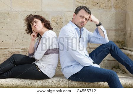 Couple In Quarrel Sitting On Bench In Park