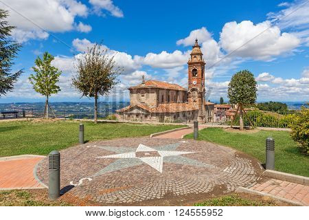Viewpoint and old parish church under beautiful sky on background in small italian town in Piedmont, Northern Italy.