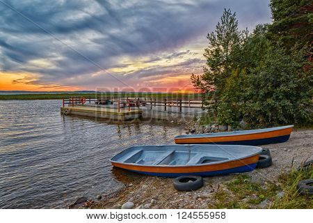 Warm Sunset view of Boats anchored at shore and Pier in the background