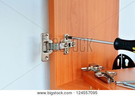 Hinge is assembled on kitchen cabinet with screwdriver