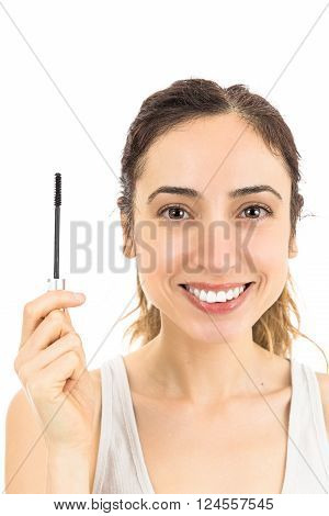 Friendly caucasian woman showing mascara brush. Isoalted on white background.