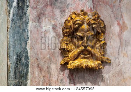 Golden fountain face of Neptune on marble wall with stream over his face
