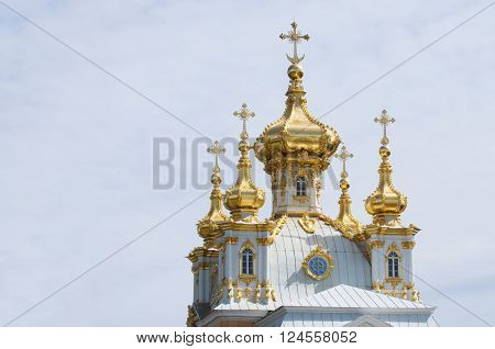 Golden shining cupola with crosses of the baroque church on sky background