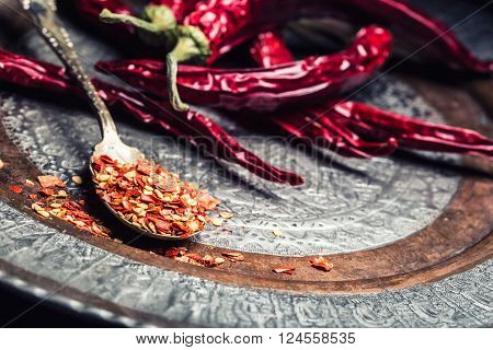 Chili. Chili peppers. Several dried chili peppers and crushed peppers on an old spoon spilled around. Mexican ingredients - cuisine.