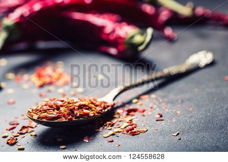 Chili. Chili peppers. Several dried chilli peppers and crushed peppers on an old spoon spilled around.