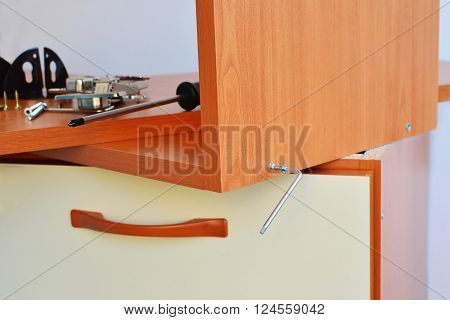 Furniture assembly screwing furniture screw with hex key wrench.