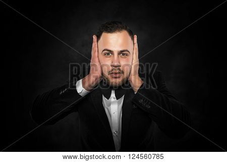 Man in suit covering his ears over dark background.