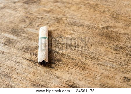 Cigarette butt discarded outdoors on the wooden table background