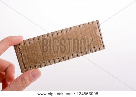 Hand holding a cut carton paper on a white background