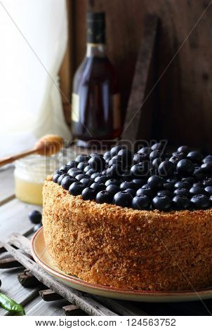 Homemade honey cake decorated with blueberry on a wooden background