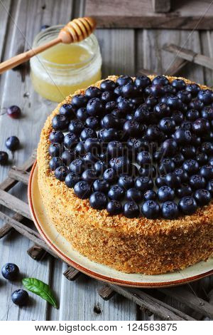 Homemade honey cake decorated with blueberry on a wooden background top view