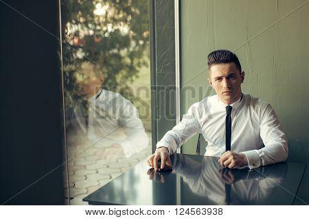 Man Sits At Table