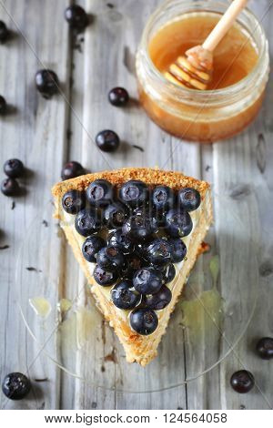 Piece of honey cake decorated with blueberry and honey on glass dish top view