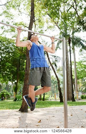 Sporty Vietnamese man doing chin-ups in the park ** Note: Soft Focus at 100%, best at smaller sizes