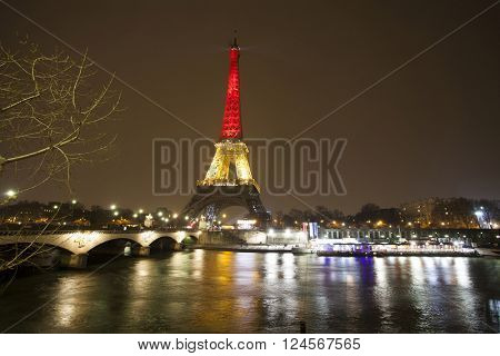 PARIS - MARCH 24: Eiffel tower illuminated with colors of the Belgian national flag to honor to victims of terrorist's attack in Brussels.