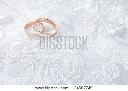 Wedding rings on wedding card, on a white wedding dress