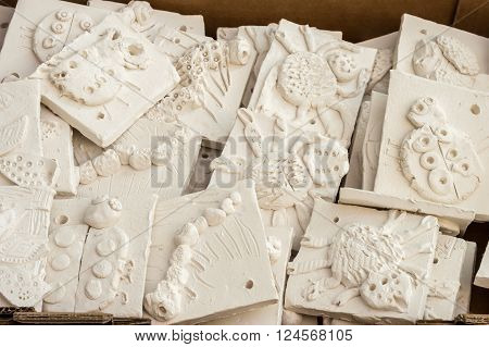 WREXHAM UNITED KINGDOM - MARCH 14 2016: Box of ceramic 'mini beasts' tiles ready to be glazed. Part of a workshop project.