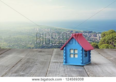 A small wooden house with blue walls and pink roof on the table from boards on the background of the city at the beach top view.