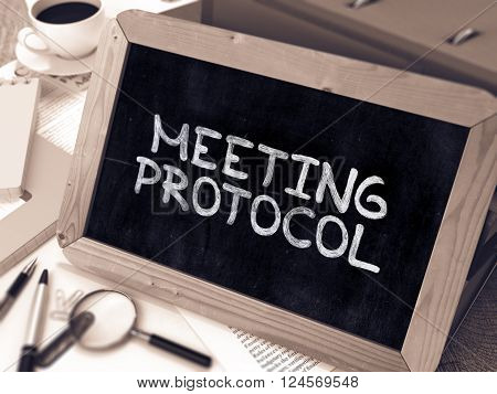 Meeting Protocol Concept Hand Drawn on Chalkboard on Working Table Background. Blurred Background. Toned Image. 3D Render.