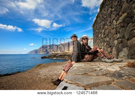 Young caucasian couple on seascape on tropical island Tenerife, Canary in Spain. Los Gigantes landscape on ocean.