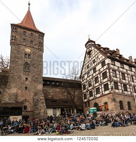 Nuremberg Germany - april 04 2016: People gathering and sitting at Tiergartner Tor Platz near Tiergaertner Tor in the old city of nuremberg.