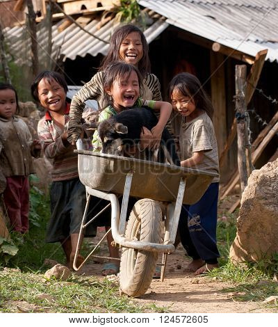 LAO CAI, VIETNAM, March 12, 2016 Lao Cai group of children playing outdoors, with a simple car