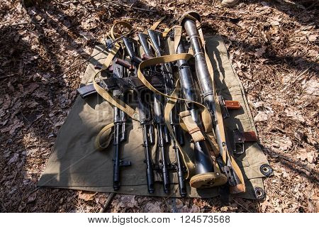Many automatic rifles and grenade launchers lie on green piece of cloth in the forest