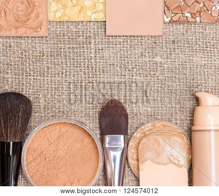 Beauty background. Cream-to-powder foundation, shimmer powder golden color, compact powder, crushed bronzing powder, loose powder, liquid foundation, makeup brushes and cosmetic sponge on sackcloth