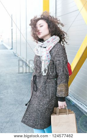 Happy girl finishes shopping. In the hands packages with purchases. Girl in a coat in the spring, wavy curly hair is developing the wind, full portrait outdoors growth. Make purchases with pleasure