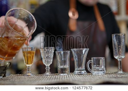 Bartender pours various of alcohol drink into small glasses on bar
