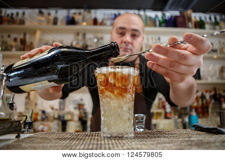 Bartender pouring cocktail into glass at the bar