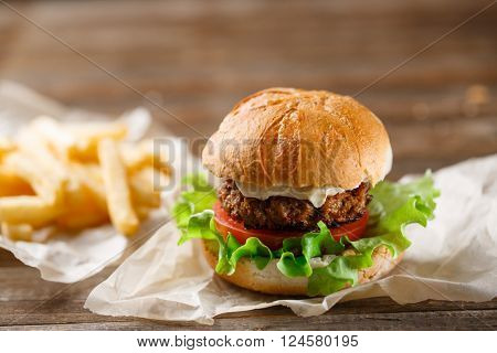 homemade burger and french fries on a wooden plate