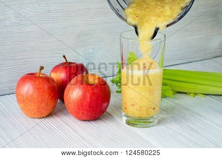 Close-up Of Smoothies From Apples And Celery Is Poured Into A Glass From A Food Processor