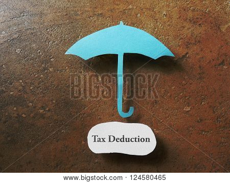 Paper umbrella over a Tax Deduction message