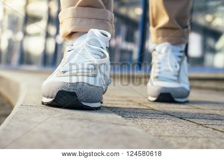 Legs in beige pants and white sneakers are on the sidewalk. Close-up, low angle shooting, shallow depth of field.