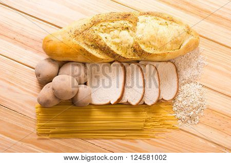 Group of carbohydrates for diet bread rice oat potatoes pasta on wood table