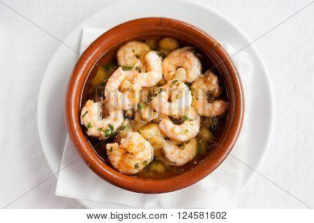 Fresh fried spanish garlic shrimp served in clay pot in local restaurant in Taganana on tropical island Tenerife Canary in Spain. Spanish food specialities.