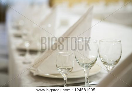 Beautifully organized event, glasses closeup at served festive white table ready.  Event in restaurant. Banquet, wedding decor, celebration. Catering and event. Wedding tables. Large restaurant hall.