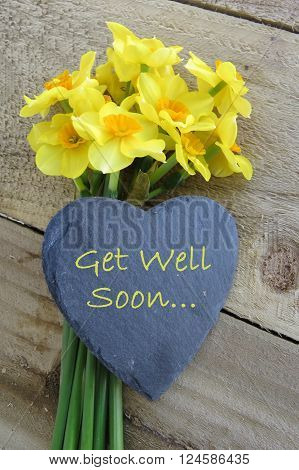 Bunch of yellow and orange daffodils with 'get well soon' text on a slate heart on a wooden background