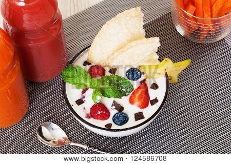 yogurt with berries and mint strawberry blueberry chocolate crumb still life, carrot sticks, juice bottles carambola