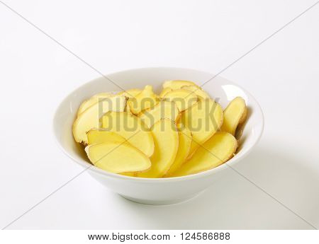 bowl of sliced raw potatoes on white background
